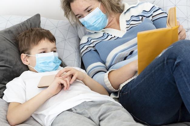 Mãe e filho com máscaras médicas na cama