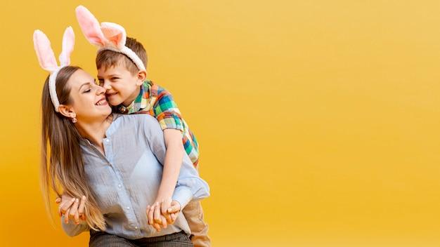 Mãe e filho com orelhas de coelho, olhando um ao outro