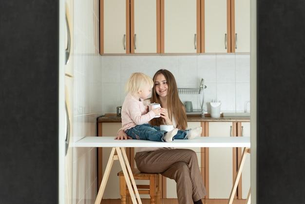 Mãe e filho comem em uma pequena cozinha bem iluminada. mãe feliz e filha loira.