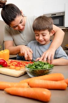 Mãe e filho cortando vegetais em dose média