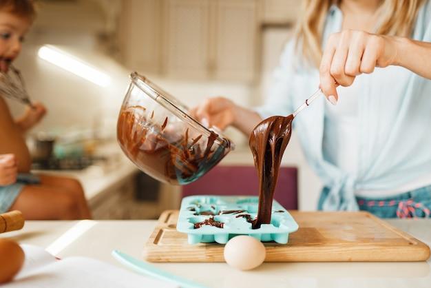 Mãe e filho cozinhando e provando chocolate derretido