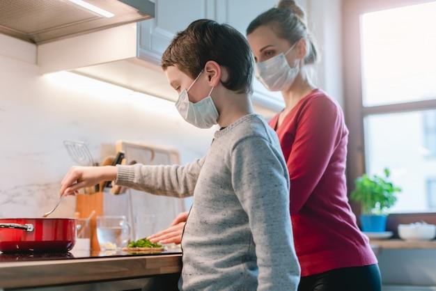Mãe e filho cozinhando em casa durante o tempo de crise