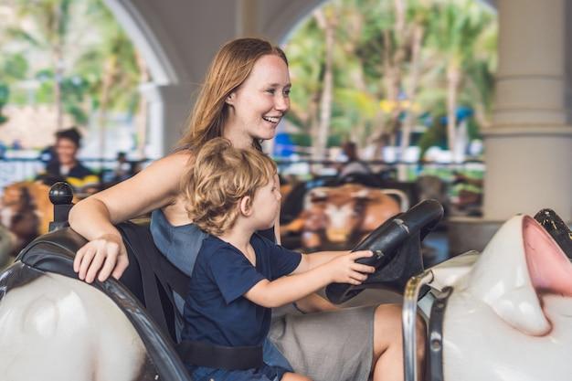 Mãe e filho dando uma volta no carro de choque no parque de diversões.