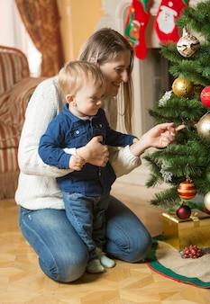 Mãe e filho de 10 meses decorando árvore de natal em casa