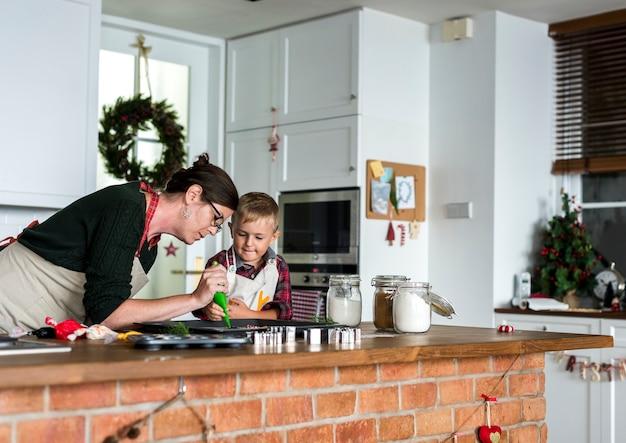 Mãe e filho de cozimento para o natal na cozinha