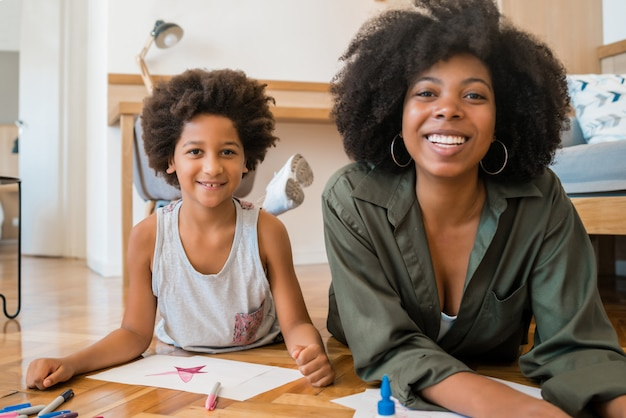 Mãe e filho de desenho com lápis de cor no chão.