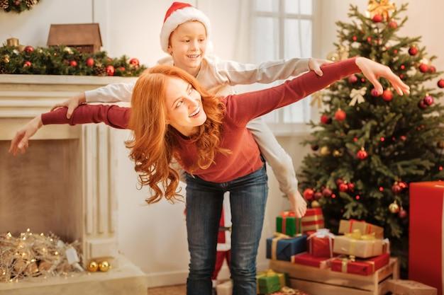 Mãe e filho de mente positiva, sorrindo amplamente enquanto fingiam voar e brincavam juntos em uma manhã de natal.