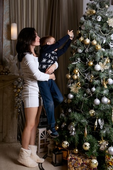 Mãe e filho decorando uma árvore de natal