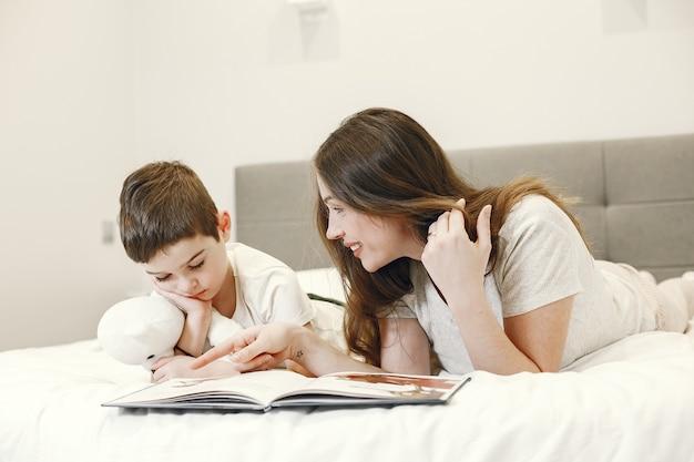 Mãe e filho deitado na cama lendo um livro.