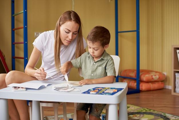 Mãe e filho desenham em uma mesa dentro da sala.