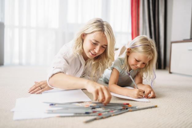 Mãe e filho desenharem no chão. sentimento dos pais, união