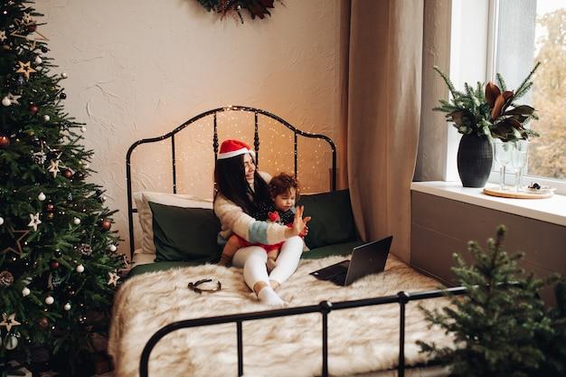 Mãe e filho dizendo olá via laptop.