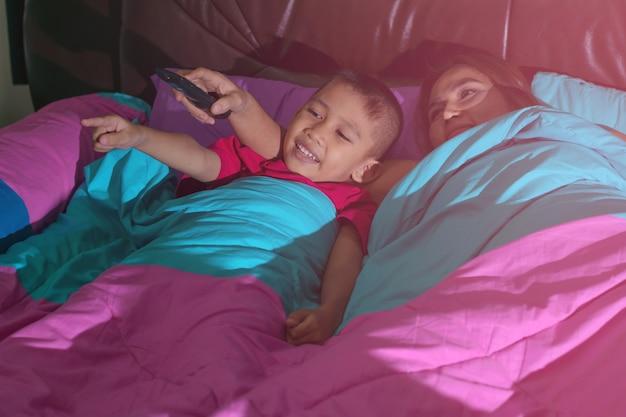 Mãe e filho dorme na cama e segura o controle remoto da tv e sorri feliz.