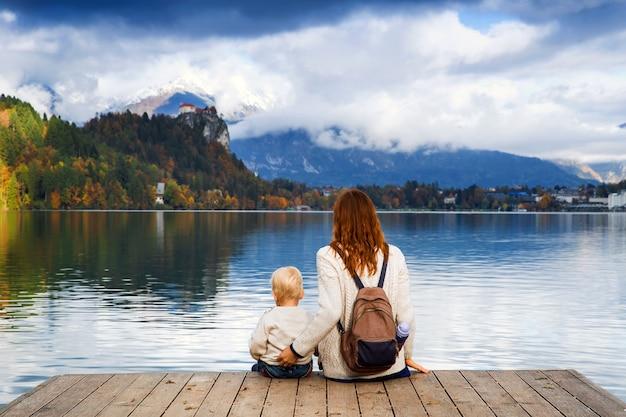 Mãe e filho elegantes sentados em um píer de madeira no lago bled, eslovênia