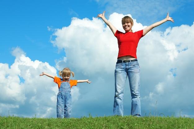 Mãe e filho em pé na grama verde com a mão aberta sob o céu com nuvens