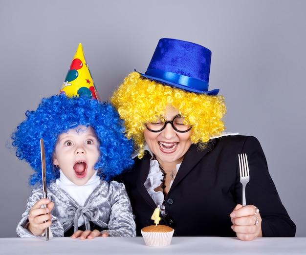 Mãe e filho em perucas engraçadas e bolo no aniversário.
