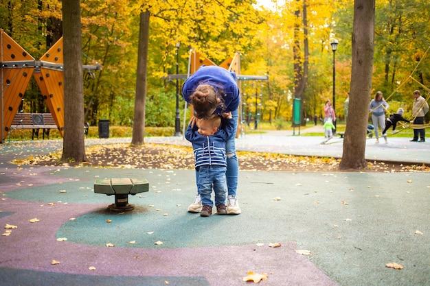 Mãe e filho em roupas azuis se divertem no parquinho no parque de outono, infância feliz