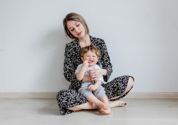 Mãe e filho em um fundo de parede branca em casa