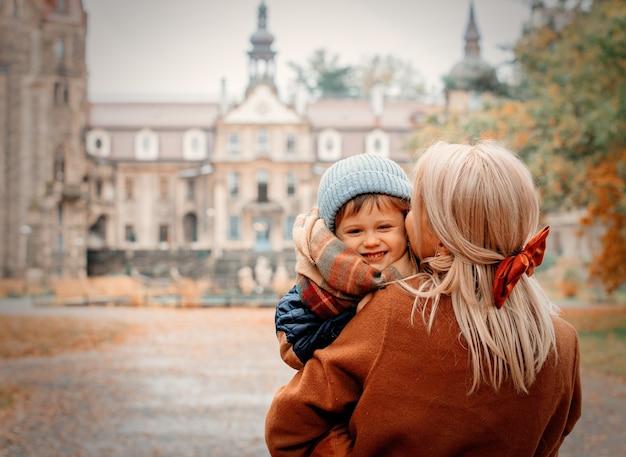Mãe e filho em um parque de outono com castelo