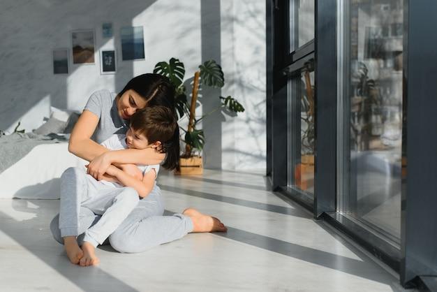 Mãe e filho engraçados no chão da sala
