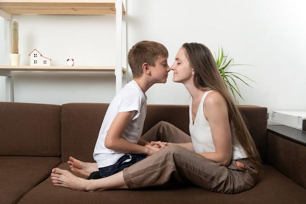 Mãe e filho esfregam o nariz enquanto estão sentados no sofá em casa. relações familiares próximas e amigáveis.