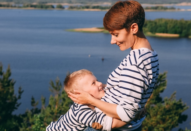 Mãe e filho estão abraçando o fundo de um grande rio
