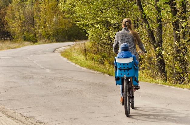 Mãe e filho estão andando de bicicleta na estrada do outono