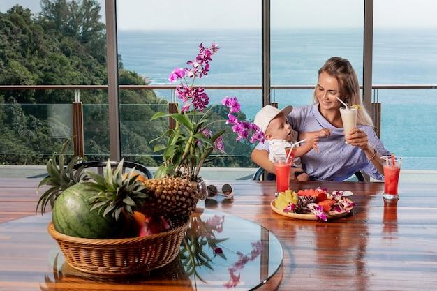 Mãe e filho estão bebendo sucos espremidos na hora de frutas tropicais