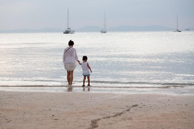 Mãe e filho estão caminhando na praia e olham para a água e os iates no mar.