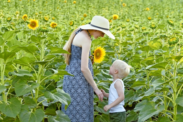 Mãe e filho estão de pé contra o campo de girassóis florescendo