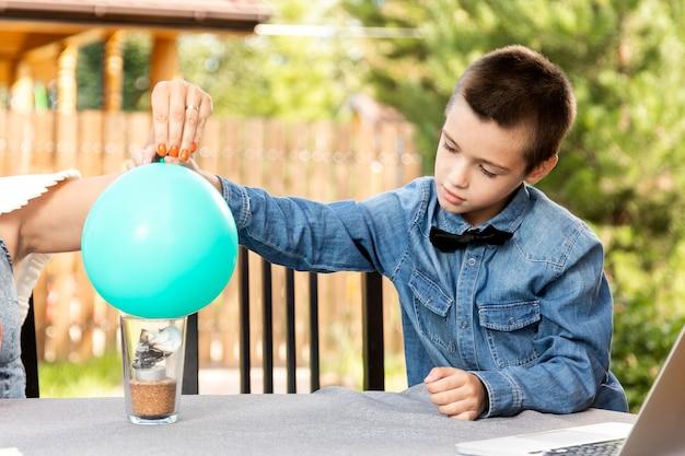Mãe e filho estão fazendo experimentos físicos em casa. uma experiência com uma criança sobre qual das bolas está vazia ou com água vai estourar mais rápido com o fogo. etapa 3