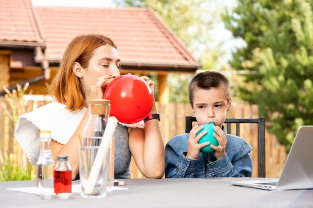 Mãe e filho estão fazendo experimentos físicos em casa. uma experiência com uma criança sobre qual das bolas está vazia ou com água vai estourar mais rápido com o fogo. passo 1