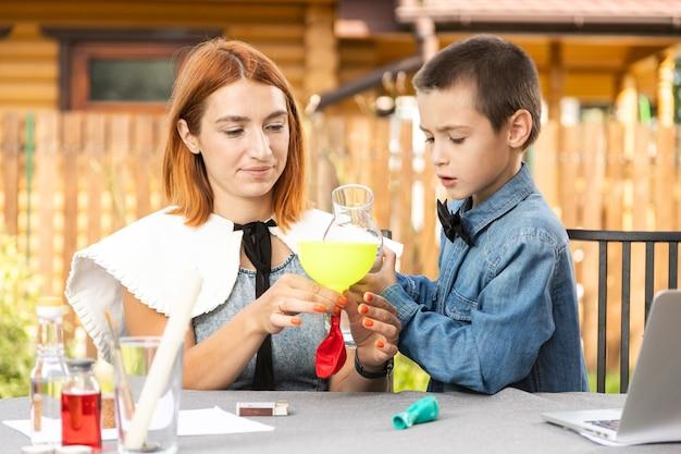 Mãe e filho estão fazendo experimentos físicos em casa. uma experiência com uma criança sobre qual das bolas está vazia ou com água vai estourar mais rápido com o fogo. passo 2