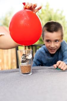 Mãe e filho estão fazendo experimentos físicos em casa. uma experiência com uma criança sobre qual das bolas está vazia ou com água vai estourar mais rápido com o fogo. passo 4