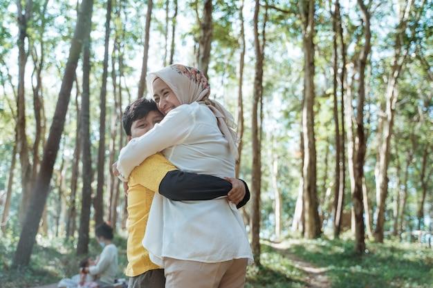 Mãe e filho estão felizes e se abraçam parados entre as árvores