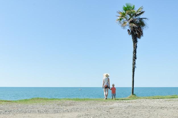 Mãe e filho estão no contexto de uma palmeira alta, mar e céu azul. vista traseira
