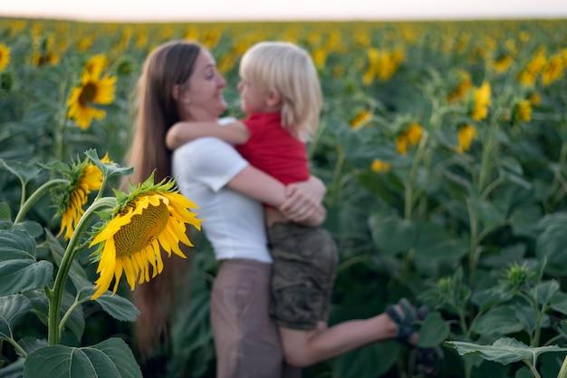 Mãe e filho estão se divertindo no campo de girassol. família feliz.