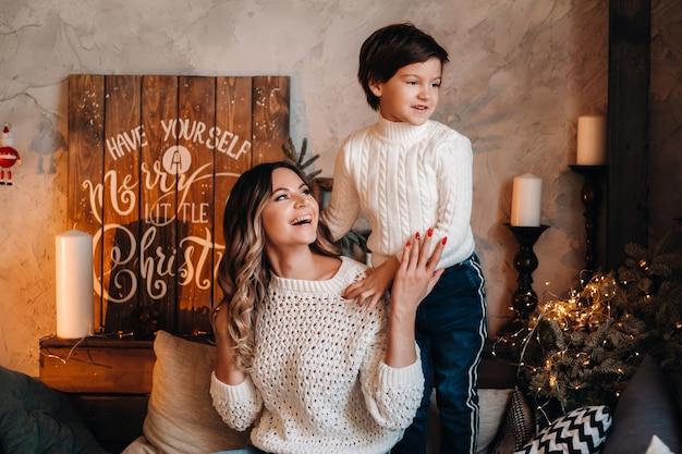 Mãe e filho estão sentados em casa no sofá antes do ano novo e sorrindo juntos.