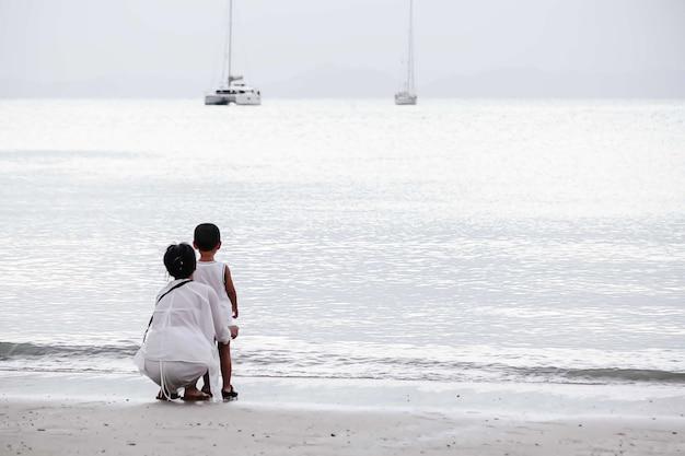 Mãe e filho estão sentados na praia e olham para a água e os iates no mar. tons de branco
