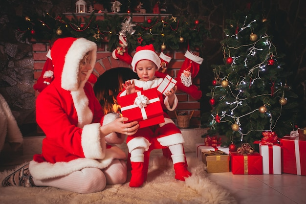 Mãe e filho estão sentados perto da lareira e abrem presentes - decorações de natal