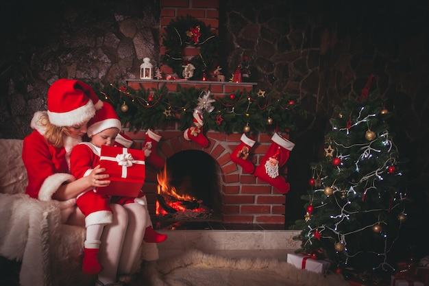 Mãe e filho estão sentados perto da lareira e da árvore de natal. família olhar para uma caixa de presente.