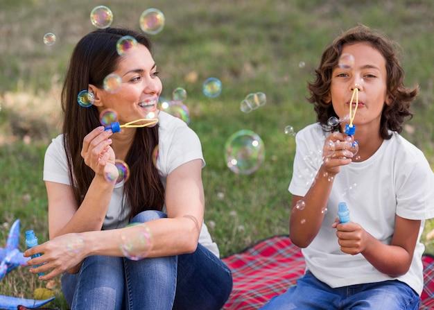 Mãe e filho fazendo balões ao ar livre juntas