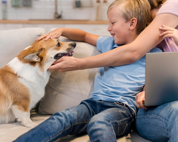 Mãe e filho fazendo carinho no cachorro da família
