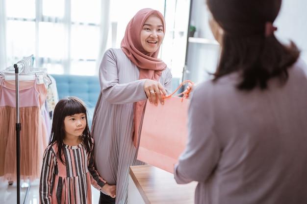 Mãe e filho fazendo compras no shopping comprando algumas roupas