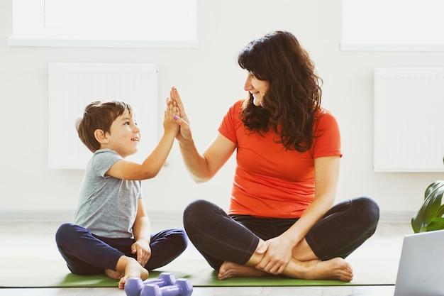 Mãe e filho fazendo exercícios em casa