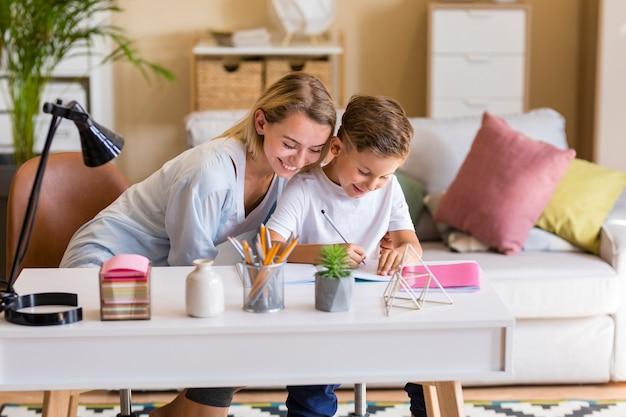 Mãe e filho fazendo lição de casa dentro de casa