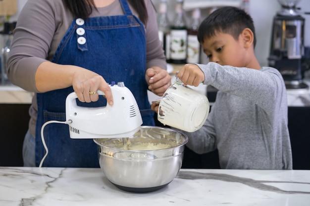 Mãe e filho fazendo um bolo
