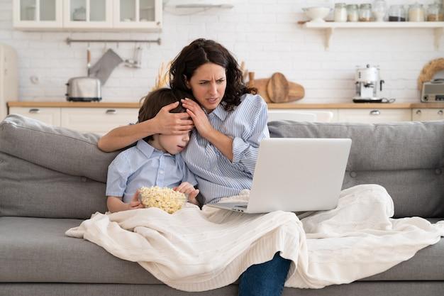 Mãe e filho filho com tigela de pipoca assistindo filme de terror fechando os olhos sentados no sofá em casa