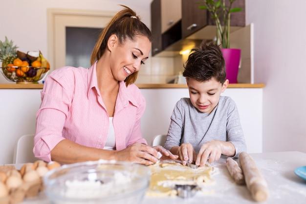 Mãe e filho filho menino estão cozinhando biscoitos e se divertindo na cozinha