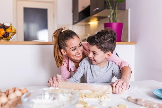 Mãe e filho filho menino estão cozinhando biscoitos e se divertindo na cozinha.